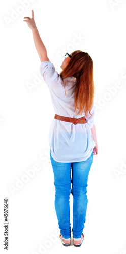 back view of pointing beautiful redhaired  woman .
