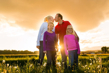 Happy family on meadow at sunset