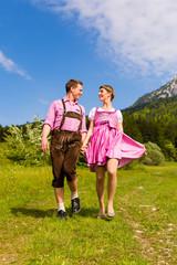 Paar in Tracht läuft auf Wiese vor Bergpanorama