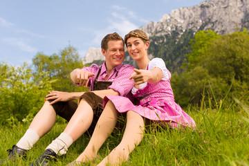 Paar in Tracht sitzt auf Wiese vor Bergpanorama