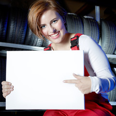 Female car mechanic presenting white message board in a garage