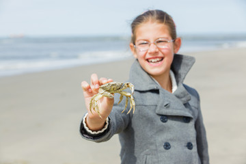 Adorable happy girl holding crab