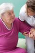 Pflegerin hilft Patientin beim aufstehen oder hinsetzen