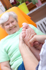 Seniorin erhält eine Fussreflexzonenmassage