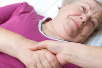 Seniorin liegt im Bett und begrüßt Pflegerin