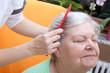 Pflegerin kämmt Seniorin durch ihr Haar