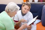 Seniorin und Pflegerin sitzen beieinander, Daten werden notiert