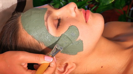 Woman with clay facial mask in beauty spa.