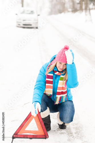 Woman put warning triangle car breakdown winter