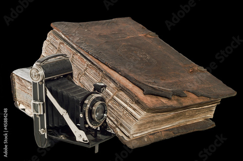 The old Christian Bible near the ancient camera. Isolated on the