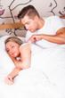 junger Mann weckt seine Freundin auf