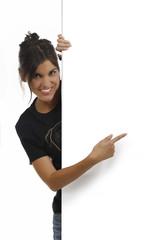 Hübsche Frau zeigt lächelnd auf leeres Plakat