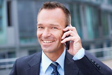 Zufriedener Manager telefoniert in der Stadt