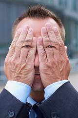 Mann mit Händen und Augen vor dem Gesicht