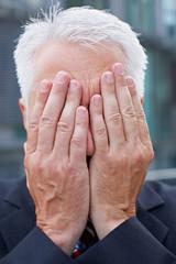 Älterer Geschäftsmann verdeckt Gesicht