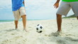 African American boys playing soccer ball on beach shot