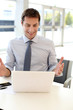 Businessman in front of laptop reading good news