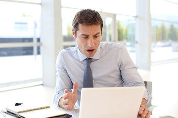Businessman with surprised look in front of laptop