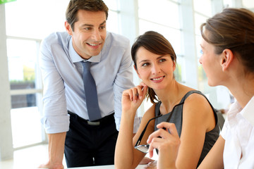 Group of business people talking around table in office