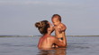 Attractive mother holds and throws up her in ocean