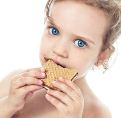 Beautiful sweet  little girl eating a cookie, FOCUS ON FACE