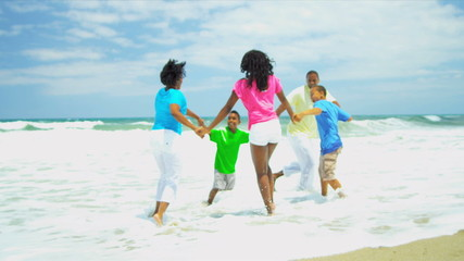 African American family have fun together on beach holding hands