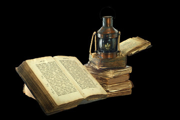 kerosene lamp and old books. Isolated on black