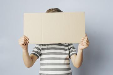 Kind hält sich ein Schild vor das Gesicht