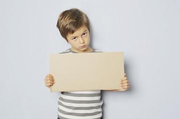 Junge hält Pappschild mit Textfreiraum