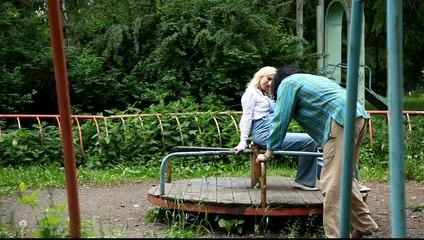 Двое влюблённых кружатся на каруселях в старом парке