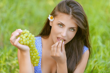 young woman sitting on grass and eating grapes