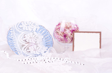 Beautiful flowers petals in glass, vintage plate and banner add