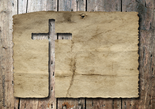 High resolution christian cross cut in an old paper on wood