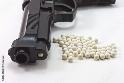 White balls with an black gun (airsoft) isolated on white - 45902658
