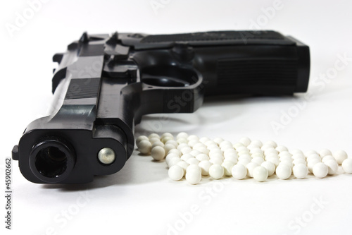 White balls with an black gun (airsoft) isolated on white