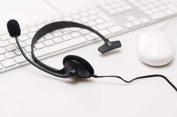 Office black headphones on white keyboard