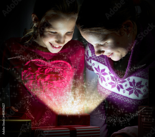 Two cute girls looking inside of a magical present
