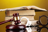 Gavel, handcuffs and.book on law on yellow background