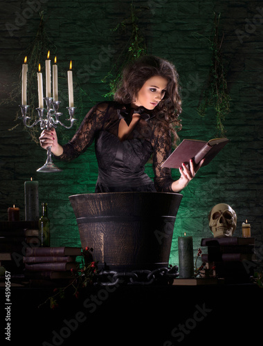 A young brunette witch in a dark dress making a mystical posion