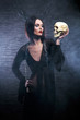 Halloween concept: young and sexy witch holding a human skull