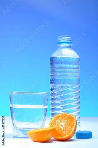 Water bottle and mandarin against blue background