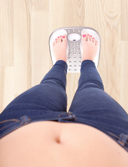 Woman on bathroom scale - diet and overweight concept