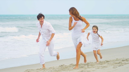 Caucasian family running and laughing together by ocean