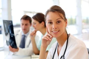 Portrait of nurse sitting in office, people in background