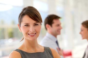 Portrait of businesswoman, team in background