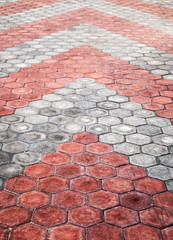 Cobblestone paving road with red and gray arrows