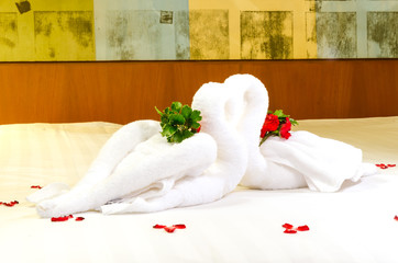 Close up of two nice towels swans on white bed sheet
