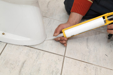 Plumber fixing toilet with  silicone cartridge, caulking