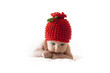 cute newborn baby in a red berry cap