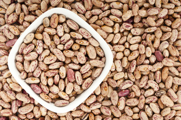 Pinto beans background with a bowl